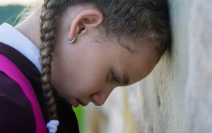 Girl leaning head on wall discouraged